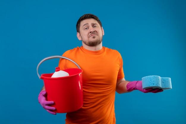 Jovem vestindo camiseta laranja e luvas de borracha segurando um balde com ferramentas de limpeza e uma esponja Foto gratuita