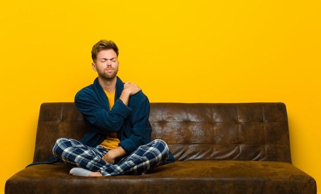 Jovem vestindo pijama sentindo cansado estressado ansioso frustrado e deprimido sofrendo com dor nas costas ou no pescoço. sentado em um sofá Foto Premium