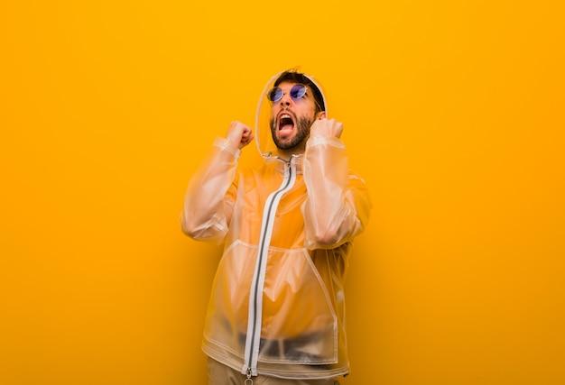 Jovem vestindo um casaco de chuva gritando muito irritado e agressivo Foto Premium