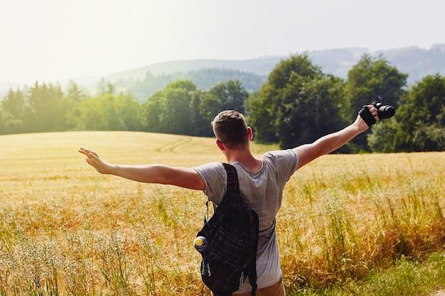 Jovem viajante abre os braços e olha para o campo de trigo dourado Foto Premium