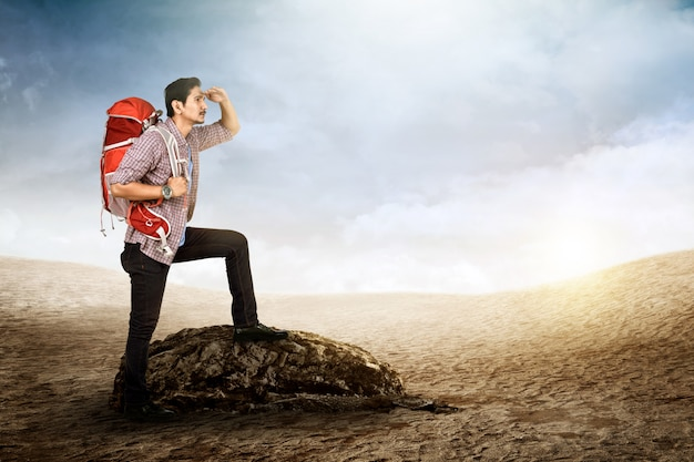 Jovem viajante asiático com mochila, olhando a vista de sua posição Foto Premium