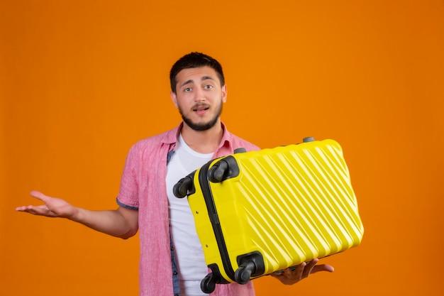 Jovem viajante bonito segurando uma mala sem noção e confuso, olhando para a câmera em pé com o braço levantado, tendo dúvidas sobre o fundo laranja Foto gratuita