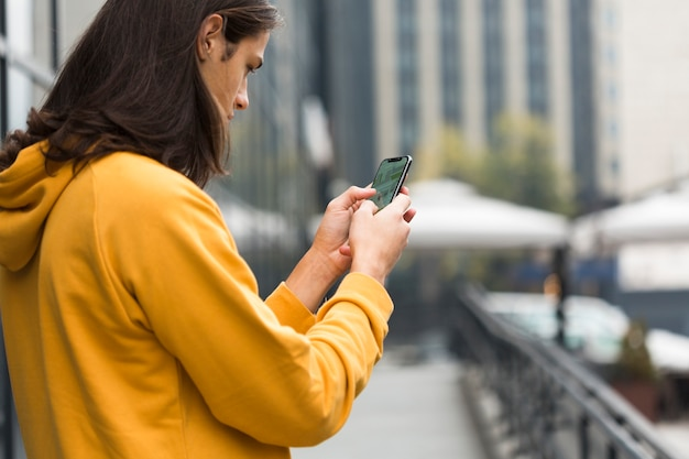Jovem viajante com cabelo comprido, verificando seu telefone Foto gratuita