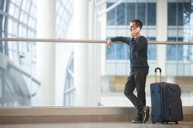 Jovem, viajante, falando, smartphone, aeroporto Foto gratuita