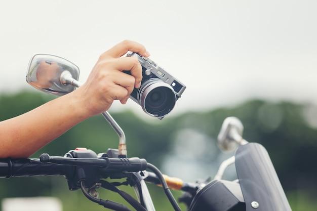 Jovem viajante masculino asiático e fotógrafo sentado na moto de estilo clássico, segurando a câmera Foto gratuita