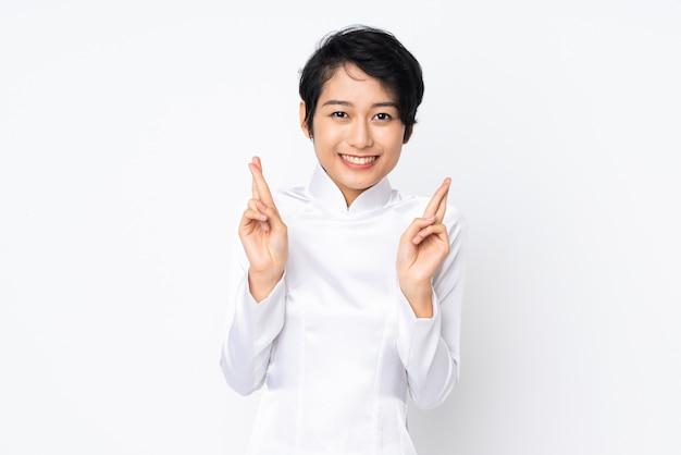 Jovem vietnamita com cabelo curto, vestindo um vestido tradicional sobre parede branca com dedos cruzando e desejando o melhor Foto Premium