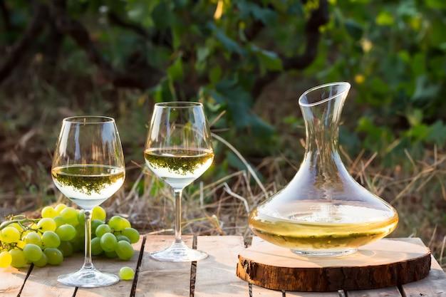 Jovem vinho branco na natureza, decanter e uvas brancas Foto Premium