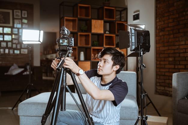 Jovem vlogger preparando a câmera para criar seu vlog Foto Premium