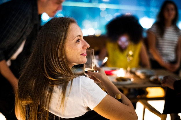 Jovens adultos jantar noite com amigos em um restaurante no terraço Foto Premium