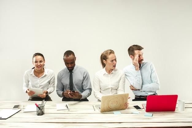 Jovens africanos e caucasianos, homens e mulheres sentados no escritório e trabalhando em laptops. o negócio, emoções, equipe, trabalho em equipe, local de trabalho, liderança, conceito de reunião. emoções diferentes dos colegas Foto gratuita