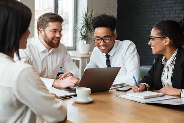 Jovens alegres colegas dentro de coworking Foto gratuita