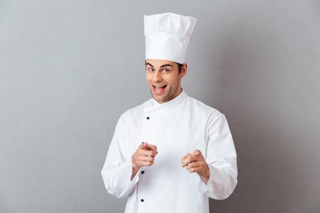 Jovens alegres cozinham uniforme apontando para você. Foto gratuita