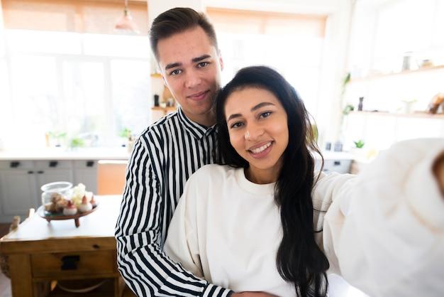 Jovens amantes abraçando e tomando selfie na cozinha Foto gratuita