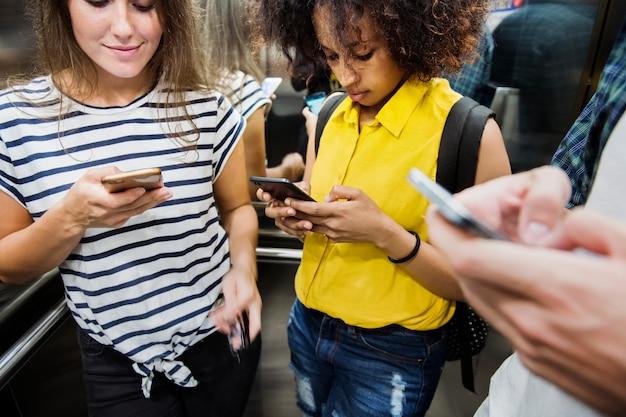 Jovens amigos adultos usando smartphones no metrô Foto Premium