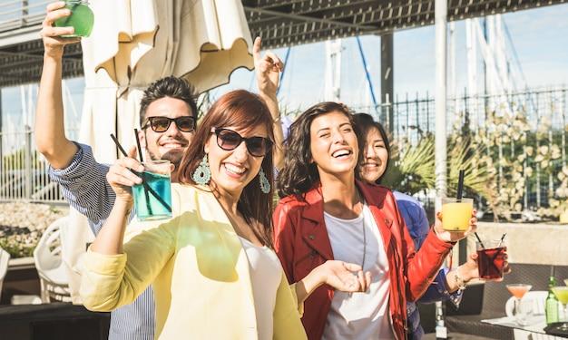 Jovens amigos bebendo e dançando na festa ao ar livre Foto Premium