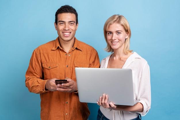 Jovens amigos com dispositivos eletrônicos Foto gratuita