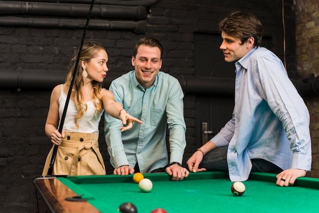 Jovens amigos conversando enquanto jogava bilhar no clube Foto gratuita