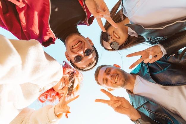 Jovens amigos de pé em círculo e mostrando o gesto de paz Foto gratuita