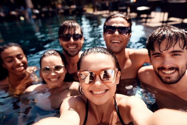 Jovens amigos felizes fazem selfie na piscina. Foto Premium