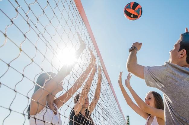 Jovens amigos jogando vôlei Foto gratuita