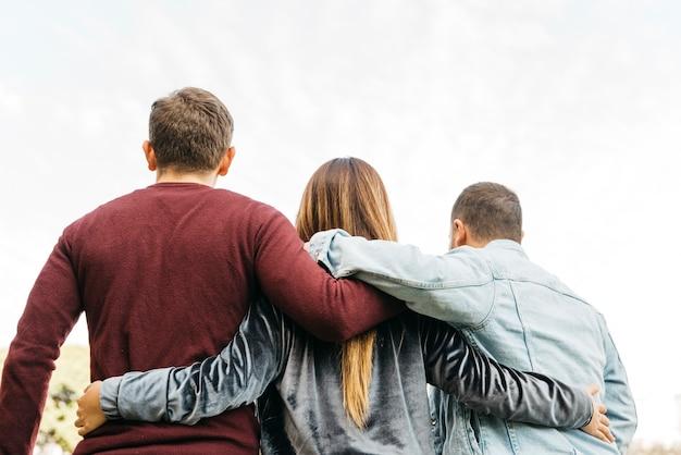 Jovens amigos próximos abraçando no dia brilhante Foto gratuita