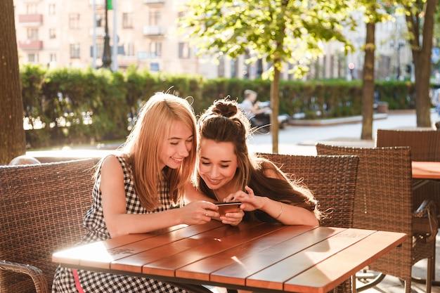 Jovens amigos sentado em um café olhando para smartphone. Foto Premium