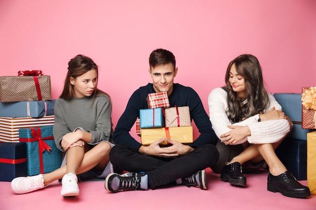 Jovens amigos sentado entre caixas de presente de natal em rosa Foto gratuita