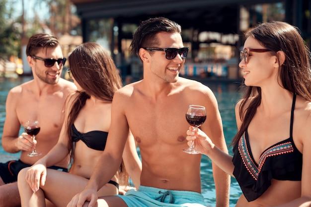 Jovens amigos sorridentes bebendo vinho à beira da piscina Foto Premium