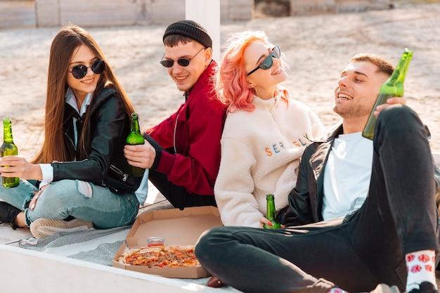 Jovens amigos sorridentes fazendo festa ao ar livre Foto gratuita