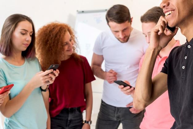 Jovens amigos usando telefones inteligentes para comunicação Foto gratuita
