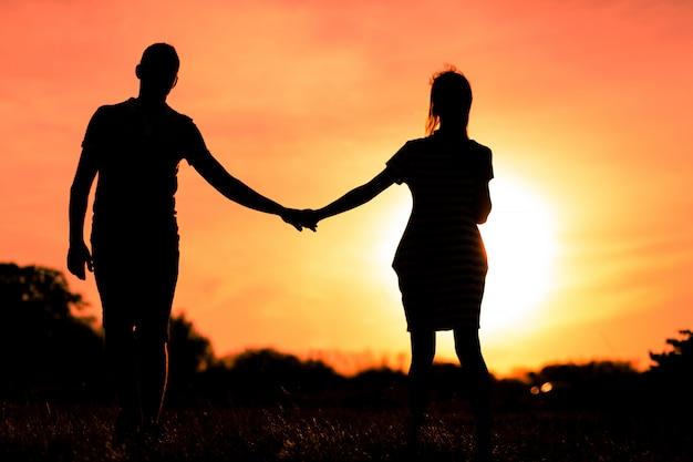 Jovens apaixonados, de mãos dadas por do sol Foto Premium
