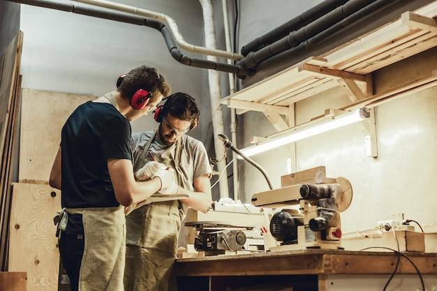 Jovens artesãos elaboração perto de bancada Foto Premium