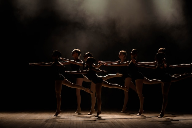 Jovens bailarinas ensaiando na aula de balé. eles realizam diferentes exercícios coreográficos e ocupam posições diferentes. Foto Premium