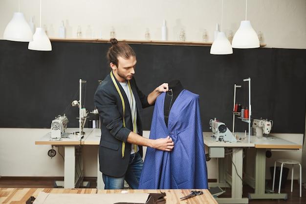 Jovens barbeado bonito caucasiano masculino estilista com roupa elegante, trabalhando no novo vestido azul para a coleção de primavera em sua oficina. artista criando roupas bonitas em sua oficina Foto gratuita