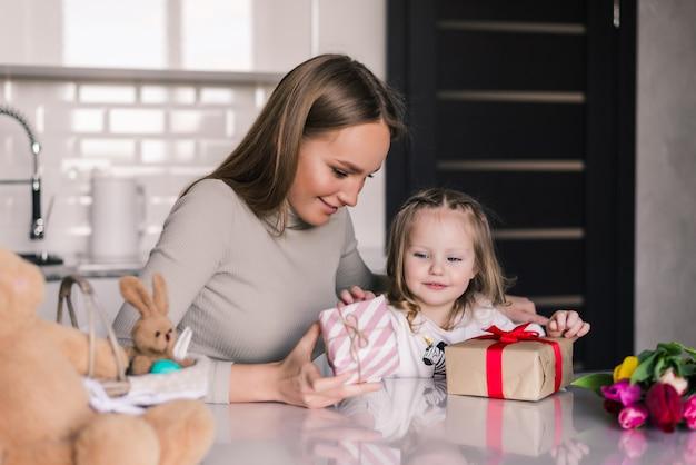 Jovens bonitas mãe e filha com caixa de presentes na cozinha Foto gratuita