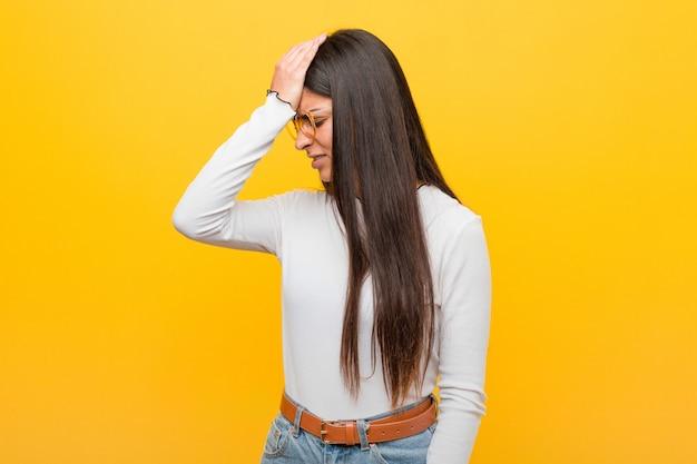Jovens bonitas mulher árabe contra uma parede amarela esquecendo algo, batendo na testa com a palma e fechando os olhos. Foto Premium