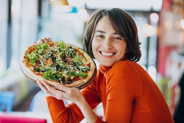 Jovens bonitas mulher comendo pizza no bar de pizza Foto gratuita