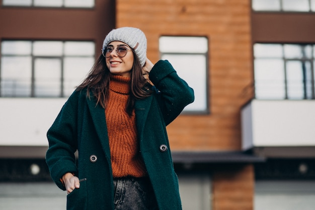 Jovens bonitas mulher de casaco quente junto à casa Foto gratuita