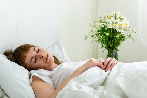 Jovens bonitas mulher dormindo no quarto com margaridas flores Foto Premium