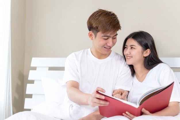 Jovens bonitas mulher e namorado bonito lendo livros na cama em casa Foto gratuita
