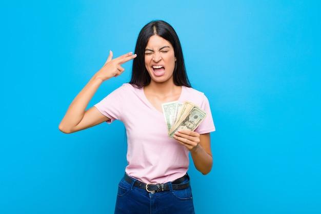 Jovens bonitas mulher latina olhando infeliz e estressado, gesto de suicídio, fazendo sinal de arma com a mão, apontando para a cabeça por cima do muro Foto Premium