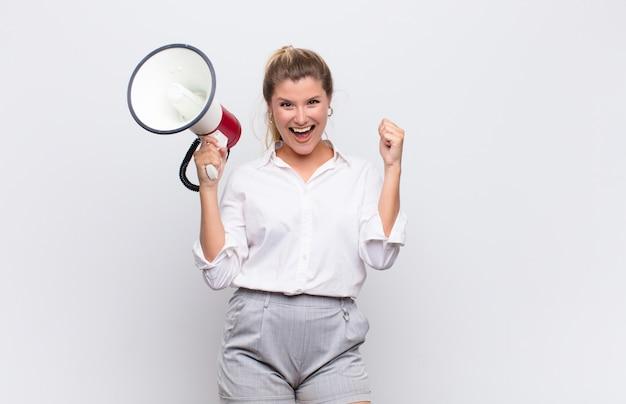 Jovens bonitas mulher latina se sentindo chocado, animado e feliz, rindo e comemorando o sucesso, dizendo uau! com um megafone contra parede branca Foto Premium
