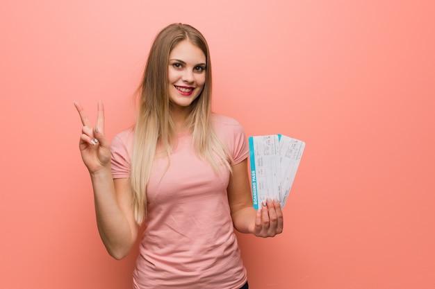 Jovens bonitas mulher russa mostrando o número dois. ela está segurando passagens aéreas. Foto Premium
