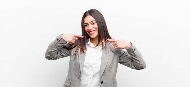 Jovens bonitas mulher sorrindo confiante apontando para próprio sorriso largo, positivo, relaxado, satisfeito atitude isolada na parede branca Foto Premium