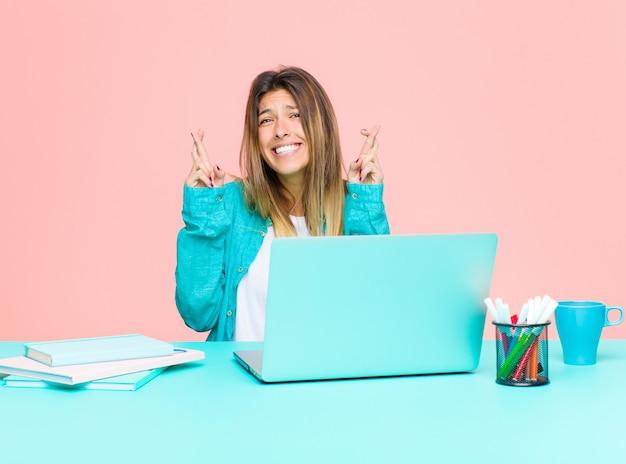 Jovens bonitas mulher trabalhando com um laptop cruzando os dedos ansiosamente e esperando a boa sorte com um olhar preocupado Foto Premium