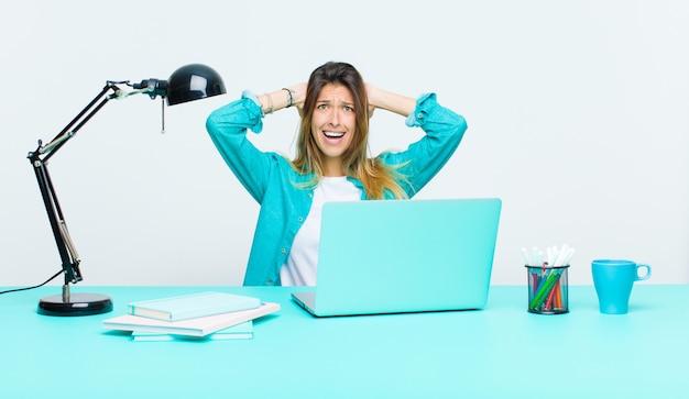Jovens bonitas mulher trabalhando com um laptop sentindo estressado, preocupado, ansioso ou assustado, com as mãos na cabeça, em pânico por engano Foto Premium