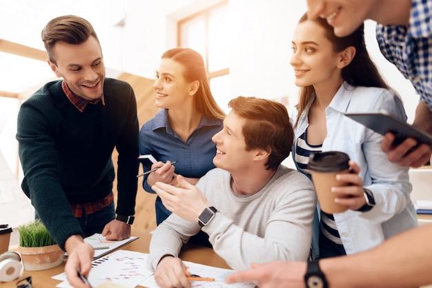 Jovens brainstorms novo plano no escritório de espaço aberto. Foto Premium