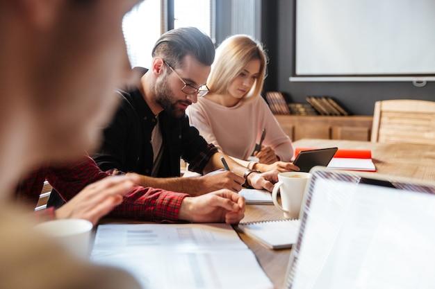 Jovens colegas atraentes sentado no escritório e coworking. Foto gratuita