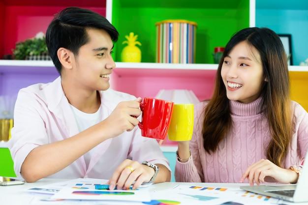 Jovens colegas bebendo bebidas durante o trabalho Foto gratuita