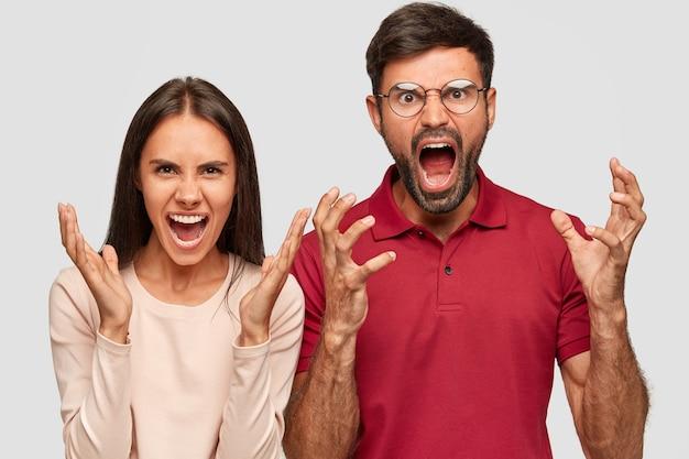 Jovens colegas frustrados e irritados, gritam com raiva, gesticulando ativamente Foto gratuita